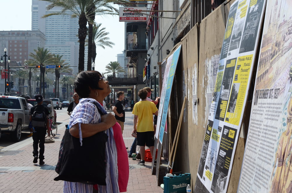 A passer-by reads installation pieces at the Canal Street site.