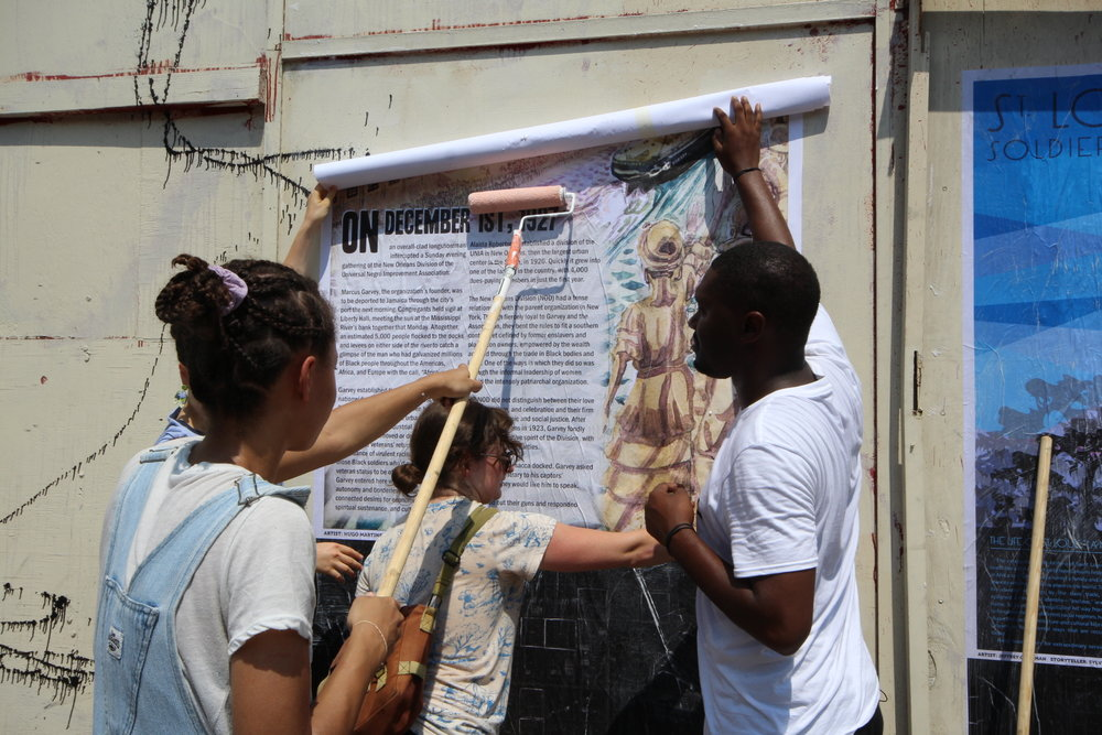 Paper Monuments volunteers Erica and Dana and co-director Bryan Lee Jr. install PMEV#023 Farewell to the Honorable Marcus Garvey at the Rampart Street site.