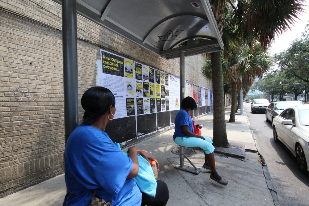 Lauren and Cynthia, passing through the bus stop, read Public Proposal panels at the Elk Place site.