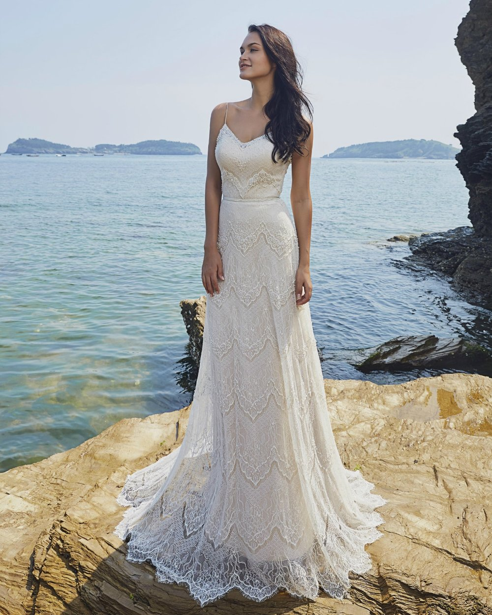 STYLIST FAVORITE - This lovely gown is crafted from all over lace adorned with hand sewn pearls. The intricately formed and repeating pattern of crests, florals and eye lash edging give this all over lace an eye catching vintage vibe. The open lace back and delicate spaghetti straps add subtle sexy touches.