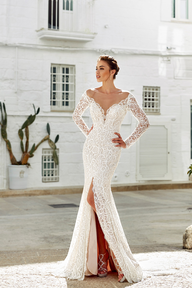 STYLIST FAVORITE - The figure hugging gown brings a unique element to the bridal world: a sexy slit! This daring style is IN and it is here to stay. Paired with elegant, long sleeves, what more are you looking for in your wedding dress? If the slit is a little on the bold side for you, it is also available with a closed slit.