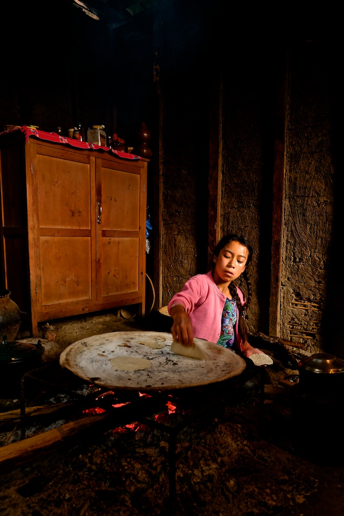 A young mayan girl in Zinacantan prepares tortillas by the original tradition in an traditional Mayan home.