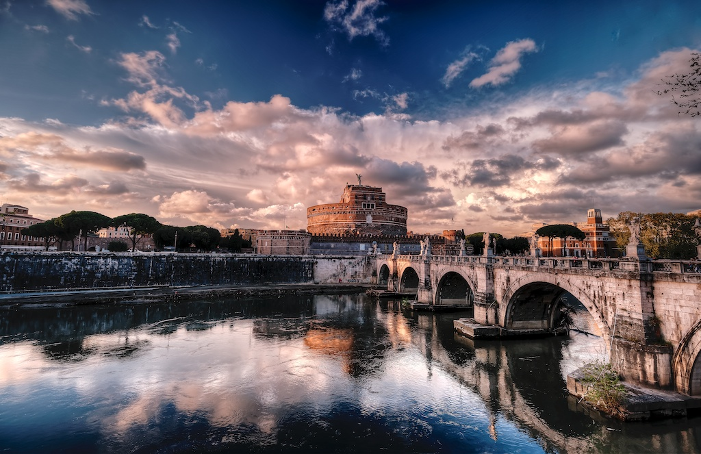 Rome, a reflection of the famous Castel Sant Angelo and Ponte Sant Angelo, on the calm water of the Tiber River at the golden hour close to sunset. My luck filled the sky with fantastic clouds providing a really dramatic background