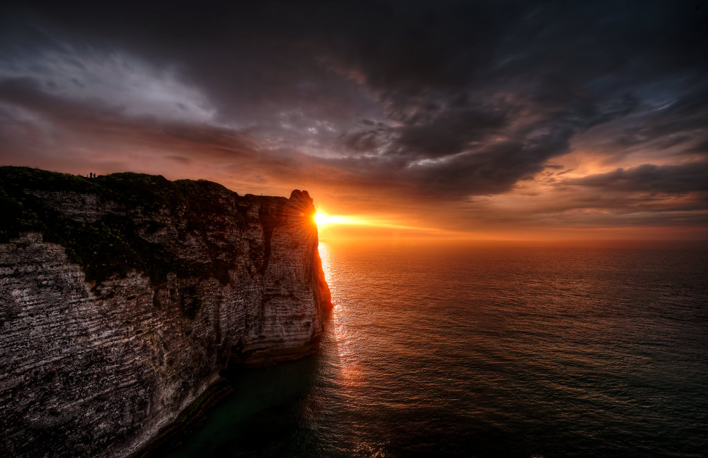 The sun sets behind a high cliff over the sea