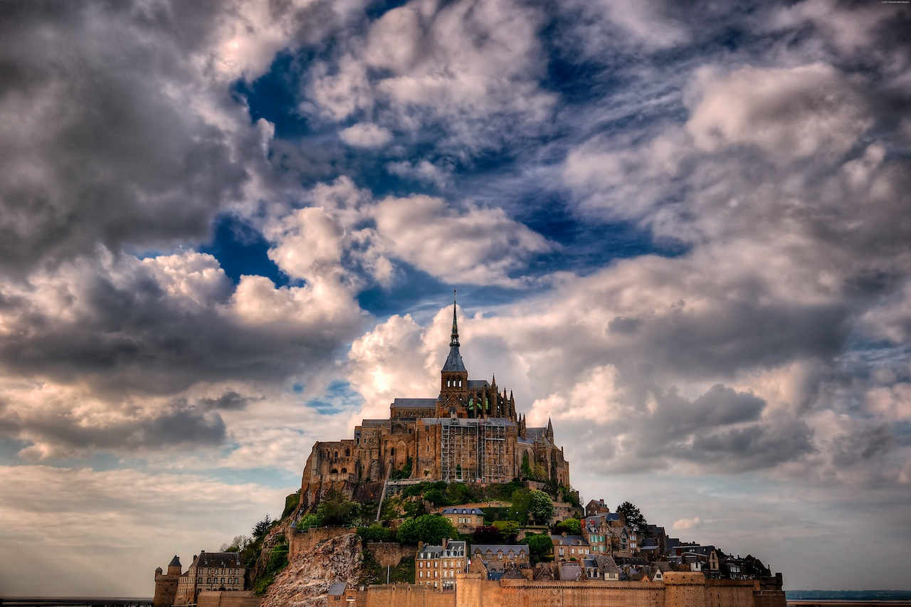A view of Mont Saint Michel under a partly cloudy sky