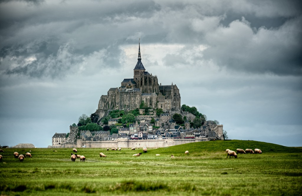 Mont Saint Michel over a field of grass with some sheeps