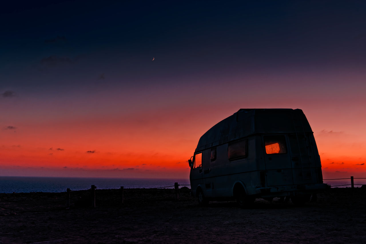 A small van enjoys the sunset and the moon