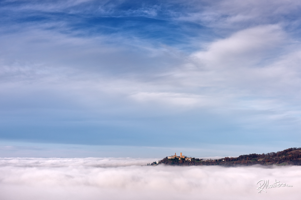 A small castle on a hill in shrouded by a sea of mist