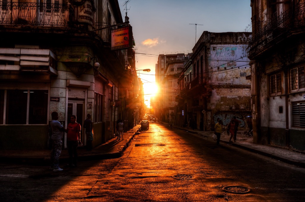 The sun sets in one of the streets in the Havana Center casting long shadows of busy people and cars.