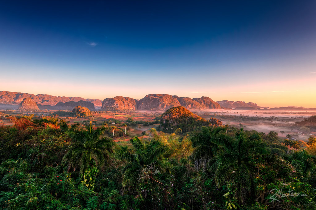 The sun rises over the Valley of Vinales in Cuba, the first rays illuminate the tops of the mogotes while the early morning fog begins to thin, uncovering the top of the palm trees. The valley of the tobacco wakes up for a work day. The detail of the photo, taken at 36 megapixels, is impressive: if printed on a large surface, palms, cows and farms can be clearly spotted.
