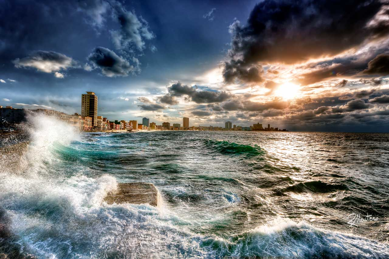 Malecon Storm - A Storm is approaching from the sea to the Havana in Cuba, big waves are leaping the wall of the famous Malecon, covering and jumping over it while the sun is breaking from some clouds to illuminate the city.
