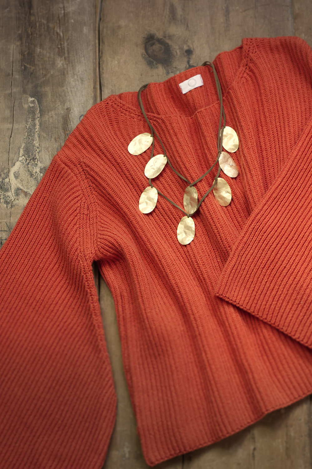 Cosy, orange jumper with bell sleeves, teamed with a gold-toned necklace.