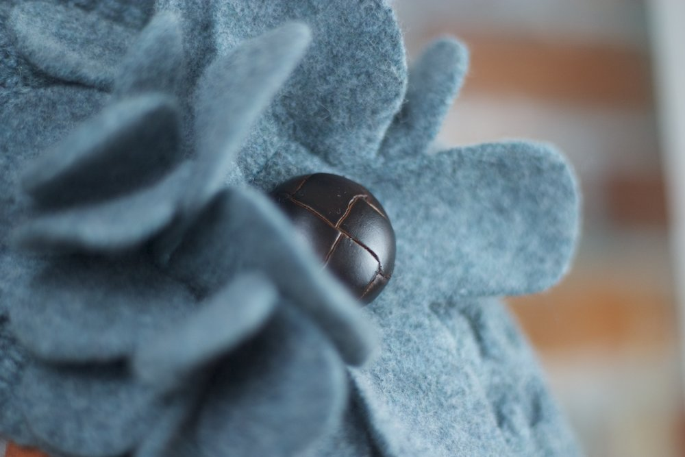 Detail of a felted flower with leather-effect button centre.