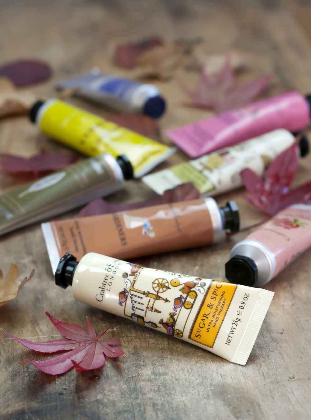 Tubes of handcream scattered among atumn leaves.