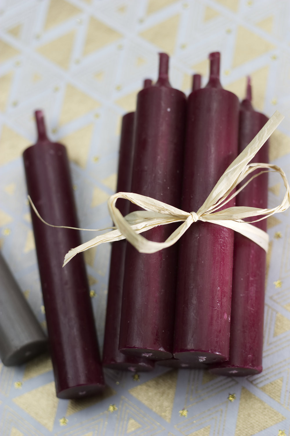 A bundle of several candles wrapped with a bow