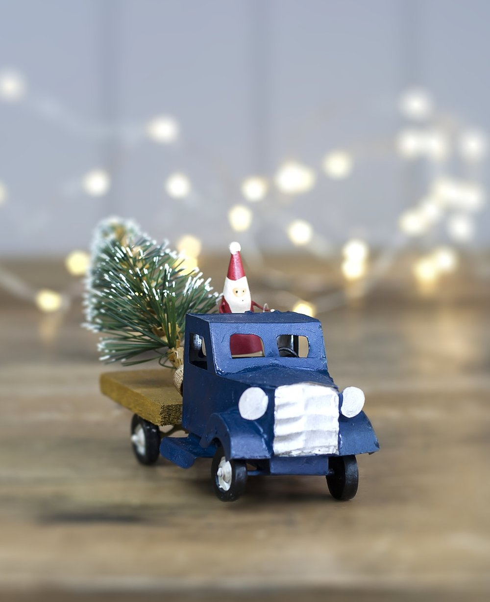 toy truck with Santa driving and a Christmas tree on the back