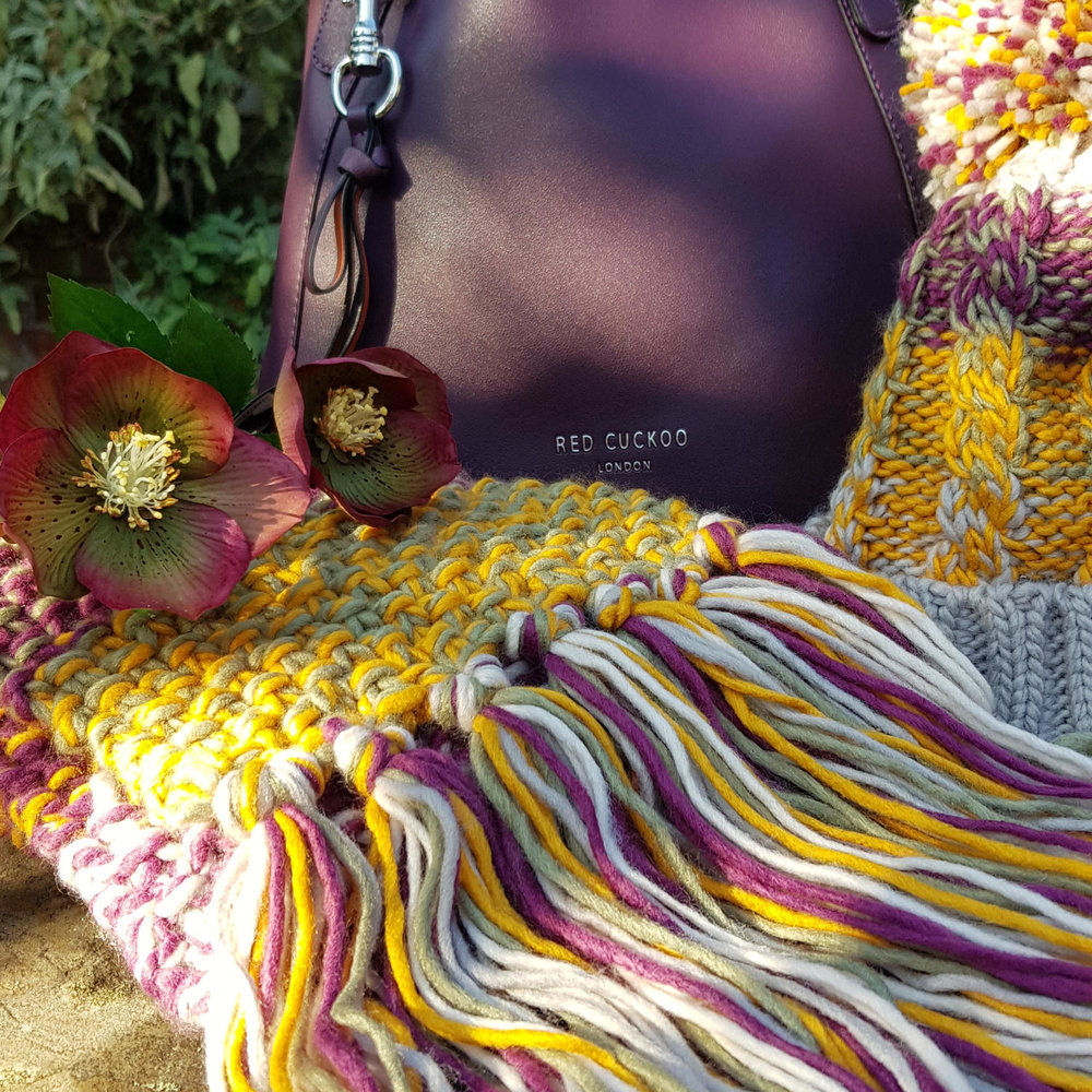 Damson purple Red Cuckoo London leather handbag and a chunky bobble hat and scarf in autumn colours.