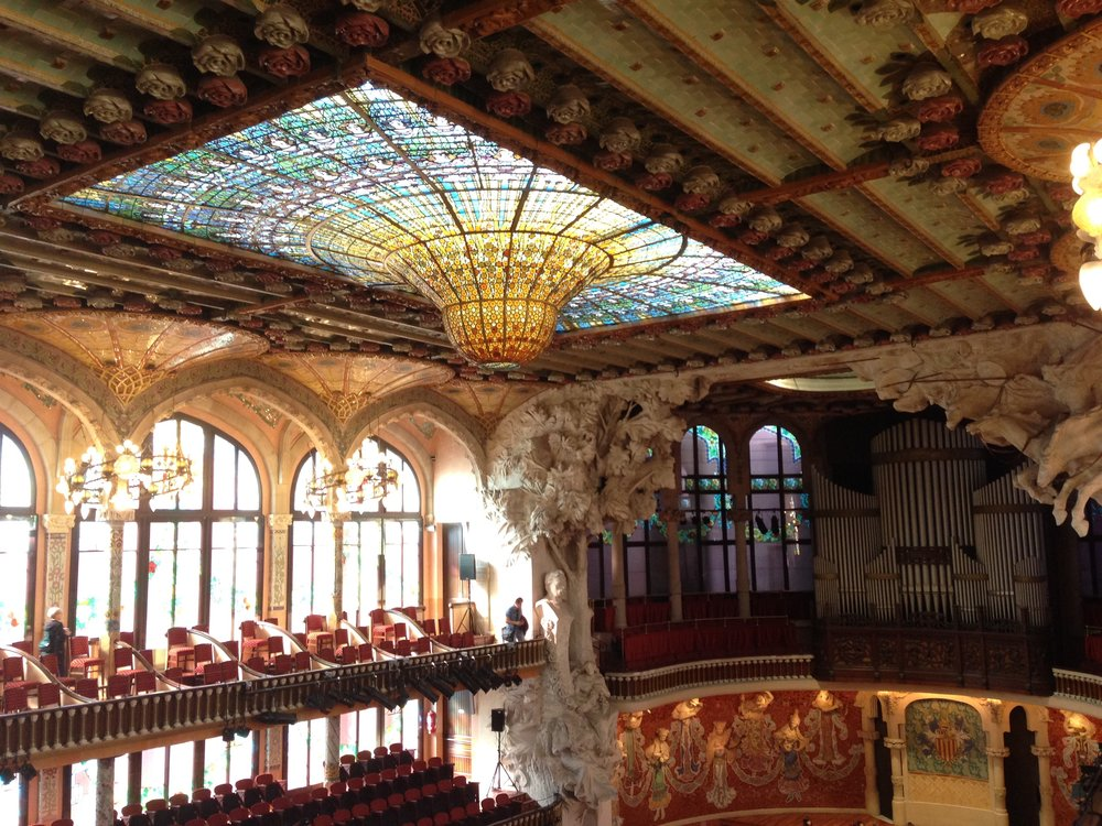 "El Palau de la Música Catalana by Lluís Domènech i Montaner is a great example of Catalan Modernism.  This place is absolutely gorgeous with all the intricate details and colours.  We see a lot of ""minimal"" architectural designs these days.  It would be nice to see the merging of both of these design concepts."