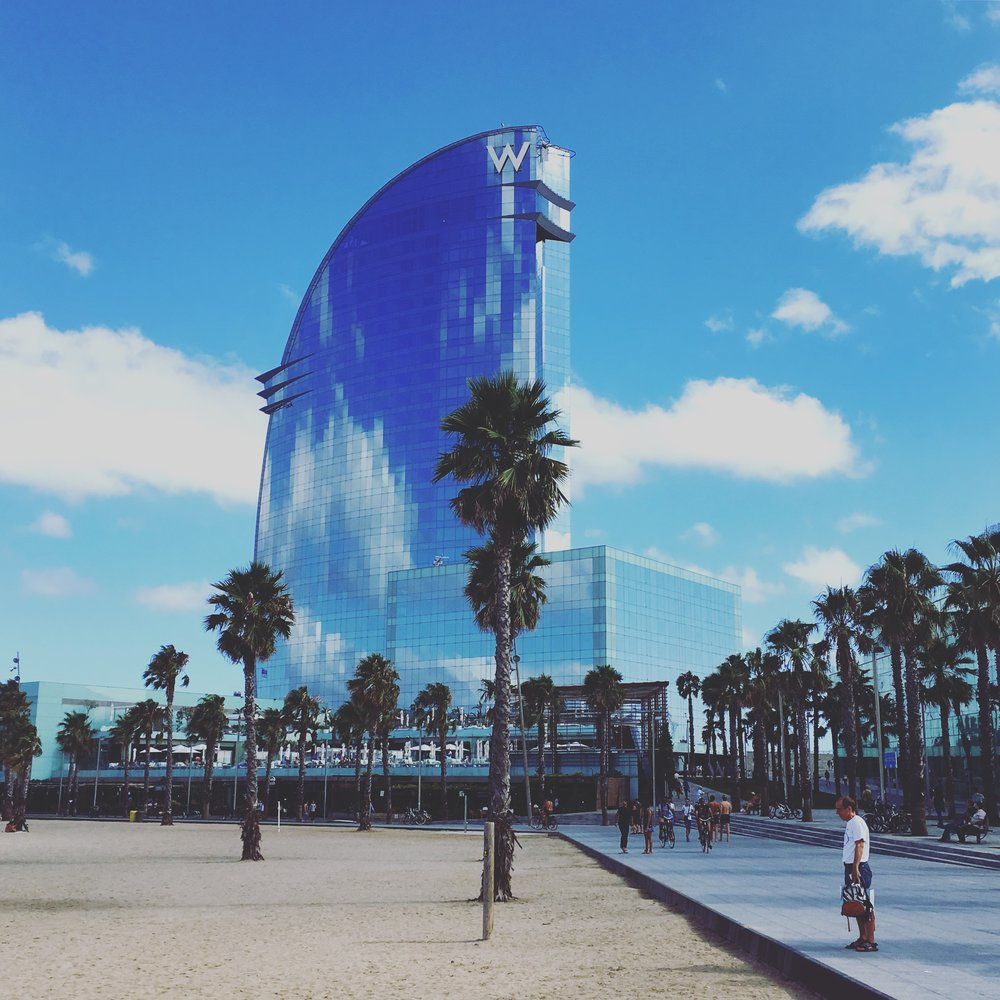 The W Hotel appears like a mirage in between the clouds and palm trees in La Barceloneta district.