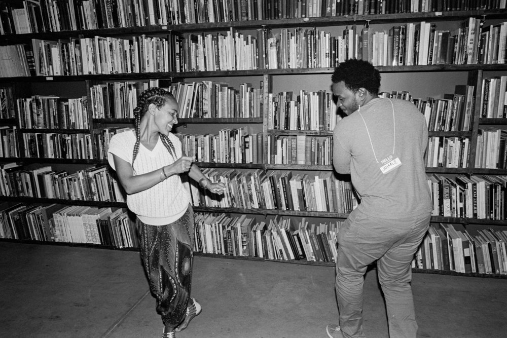 Two black artists dance carefree in front of a large bookshelf. Photo is in black and white.