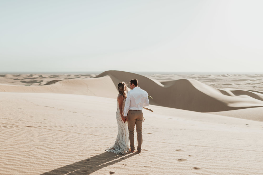 ScottTiffany (24 of 48).jpgcouple walking in sand dunes together at imperial sands california elopement destination