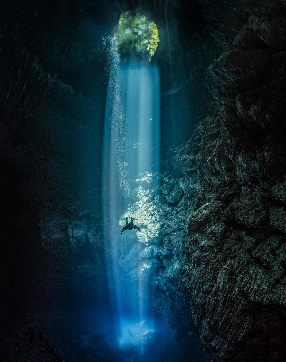 """This shot is using the beam of light streaming down from the jungle above, as the main subject in shot. With a diver in the beam illuminated inside the famous Pit cenote in the Yucatan in Mexico. Technically it's all about underexposure, no strobe is used only the available light, which there actually isn't a lot of. So whilst it's not hard to shoot the light itself, and you can't actually see the sun as it's above the jungle canopy, you are actually shooting at the limits of what the camera can record in the gloomy interior"""