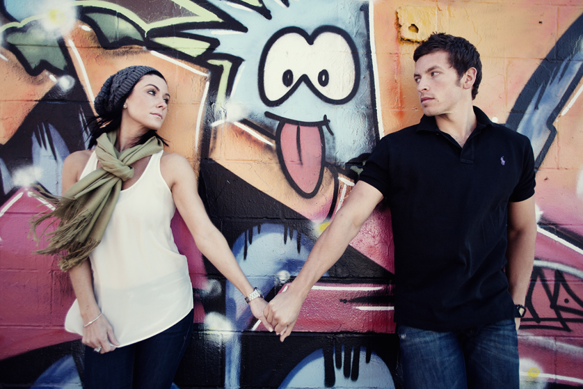 Couple holds hands in front of graffit wall