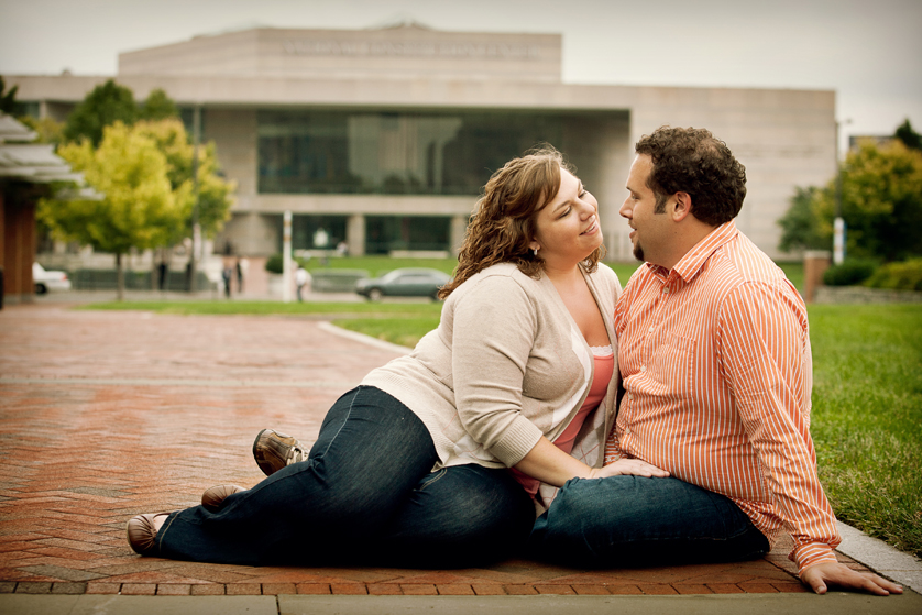 Couple sitting in Old City with National Constitution Center behind them in Philadelphia, PA