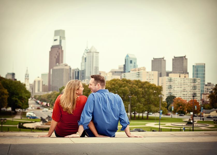 Couple sitting at top of Art Museum steps with Philadelphia skyline behind them