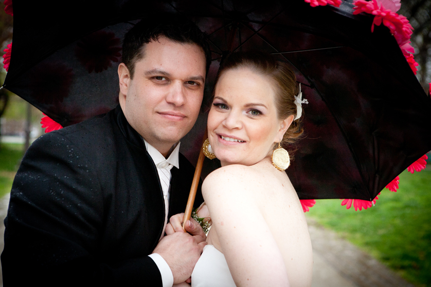 Bride and groom smile from under a black umbrella