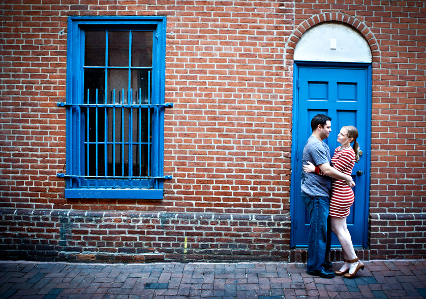 Urban engagement photo of couple in front of bright blue door and brick wall