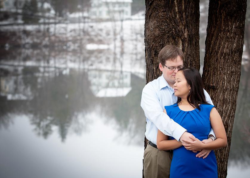Winter scene is reflacted in water behind couple cuddling by tree