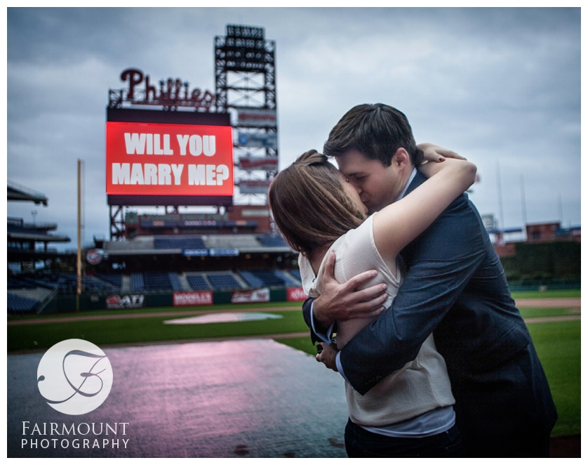 Newly-engaged couple kiss on field at Citizen's Bank Park