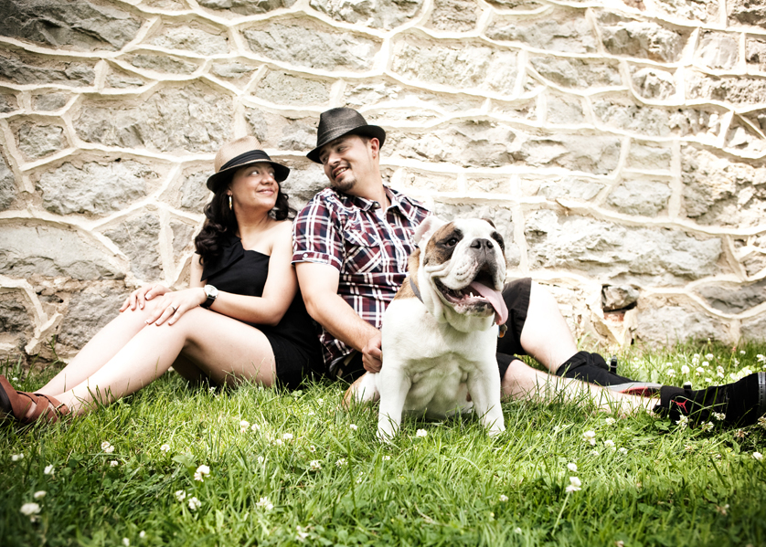 Vintage-style engagement portraits with bulldogs by old stone wall