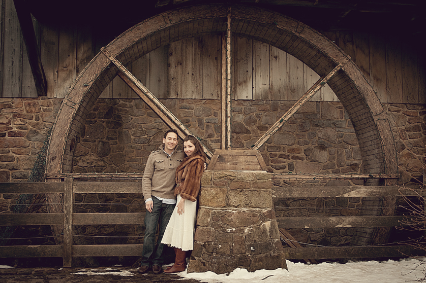 Couple standing in front of water wheel at mill in Peddlers village