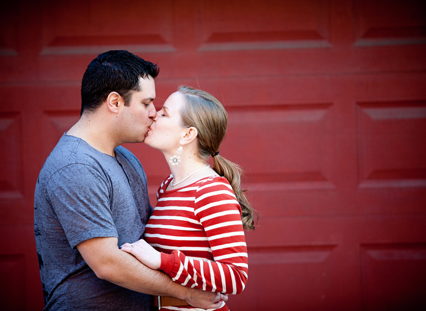Kissing couple framed by red wall in Philadelphia, PA