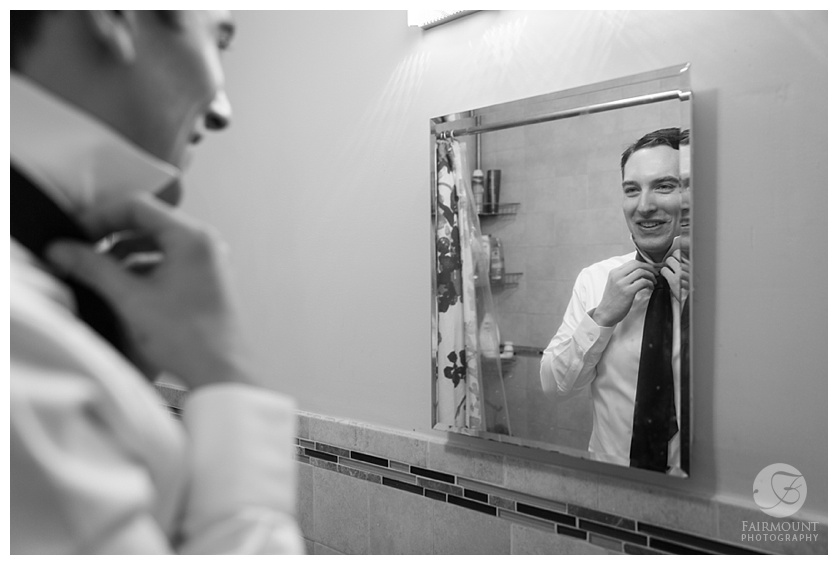 Groom getting ready in mirror.