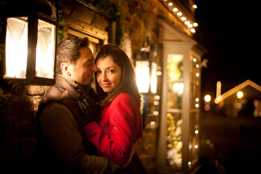 Warm glow of christmas lights for engagement photo at Peddlers Village