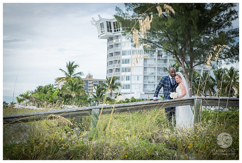 Bride and groom on bridge at beach
