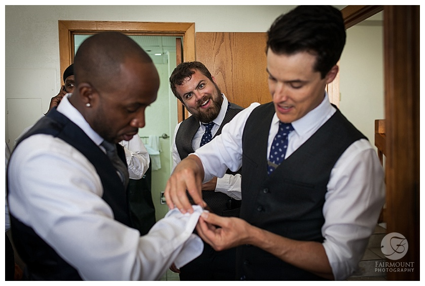 Groomsman putting cufflinks on groom