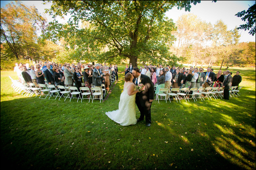 Married couple kiss under a big tree after a fall wedding ceremony