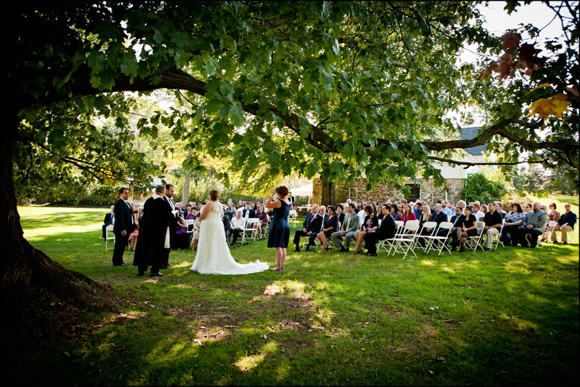 Bride and groom hold hands under a beautiful tree during their ceremony in Bethlehem, PA