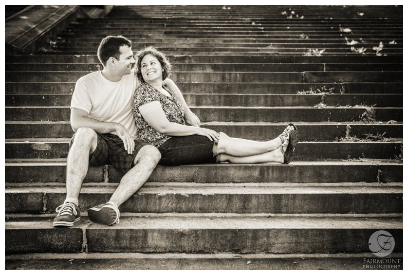 Couple smiles at each other on the steps behind the Philadelphia Museum of Art