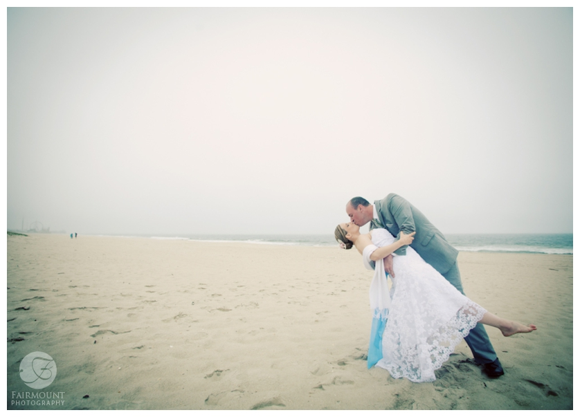 groom dips bride for a kiss on the beach