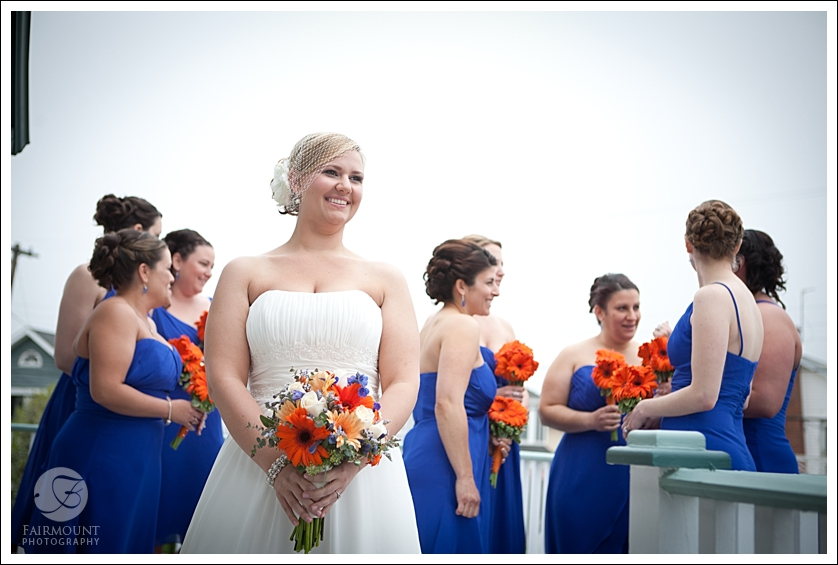 Candid bridesmaids photo blue bridesmaids dresses and orange bouquets