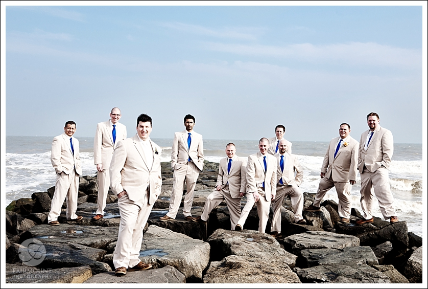 Groom and groomsmen on rocks in ocean