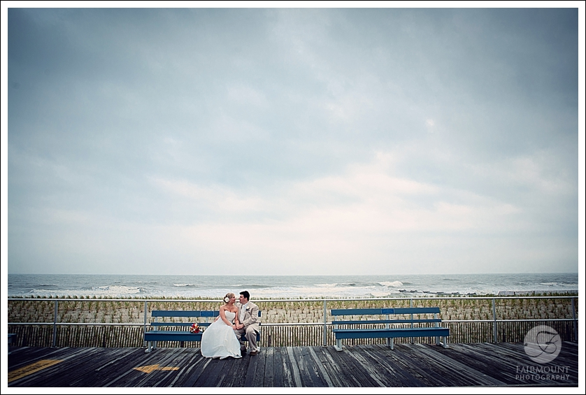 Wedding portrait on Ocean City boardwalk with cloudy sky and ocean