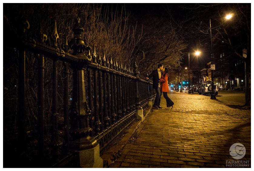 Engagement photo by wrought iron gate around the Boston Public Garden at night