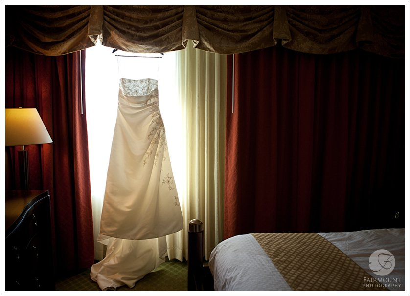 wedding dress in window with red curtains