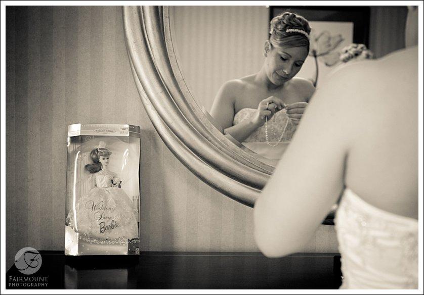 bride puts on jewelry with wedding day barbie on dresser